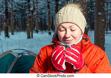 portrait of a beautiful girl with a mug of hot tea in a winter forest