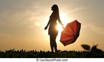 portrait of a beautiful girl with a red umbrella in the sunset