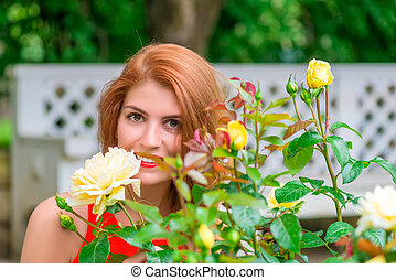 portrait of a beautiful girl with a rosebush