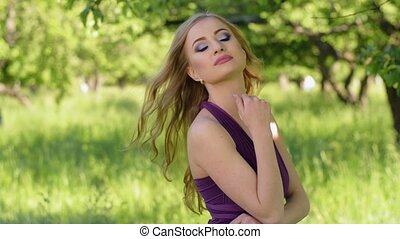 Portrait of a beautiful girl with bright make-up. Caucasian blonde woman posing and looking at camera in lilac or purple dress in green garden near apple fruit tree.