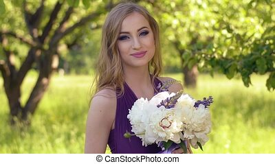 Portrait of a beautiful girl with bright make-up. Caucasian blonde woman with a bouquet of flowers posing and looking at camera in lilac or purple dress in the garden.