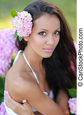 portrait of a beautiful girl with flowers in the summer