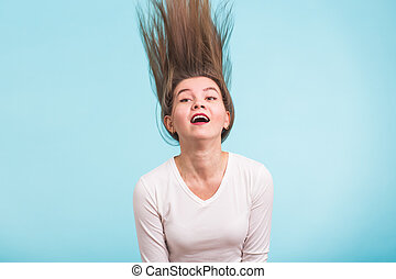 Portrait of a beautiful girl with flying hair on blue background