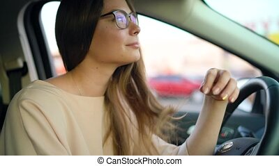 Portrait of a beautiful girl with glasses in the car