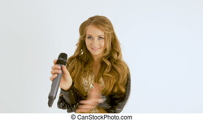 Portrait of a beautiful girl with long hair. She claps her hands together with the music. close-up