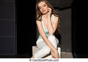 Portrait of a beautiful girl with long hair sitting