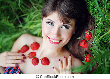 portrait of a beautiful girl with strawberries in the park