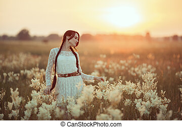 Portrait of a beautiful girl with white flowers on the summer field in sunlight.