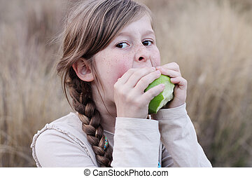 portrait of a beautiful happy girl eating green apple
