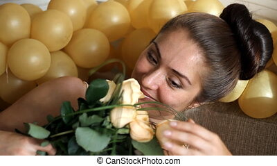 Portrait of a beautiful happy young girl enjoying the scent of a bouquet of creamy roses on a background of golden balls, looking at the camera and smiling. Close-up.