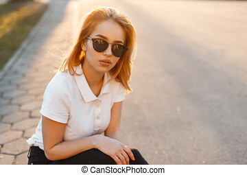 Portrait of a beautiful hipster young woman in stylish sunglasses in a white polo t-shirt in black jeans at sunset. American girl is sitting on an asphalt road.