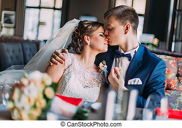 Portrait of a beautiful kissing couple  in vintage cafe. Wedding day. Close up. Indoor shot