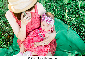Portrait of a beautiful, laughing girl with gorgeous blue eyes being held by her mother, on her back, in her lap in the garden.