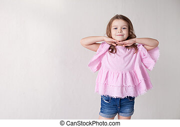 Portrait of a beautiful little girl in a pink dress five years