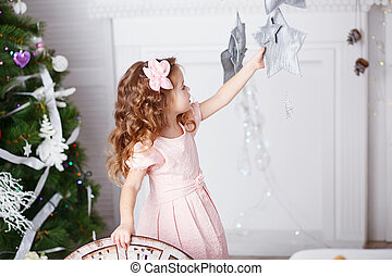 Portrait of a beautiful little girl in a pink dress in the interior with Christmas decorations.