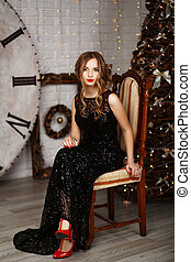 Portrait of a beautiful long-haired young girl in black Evening Dress