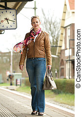 Portrait of a beautiful mature woman standing on train station platform