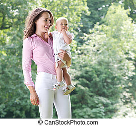 Portrait of a beautiful mother holding baby in the park