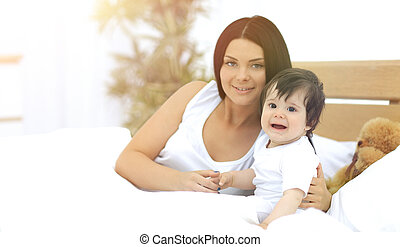 Portrait of a beautiful mother with her baby in the bedroom