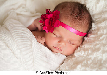 Headshot of a sleeping 8 day old newborn baby girl wearing a pink flower headband. She is wrapped in white gauzy fabric and sleeping on her back on a white billowy blanket.