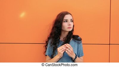 Portrait of a beautiful pensive girl with red hair on orange...