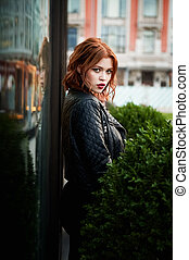 Portrait of a beautiful redhead. Fiery hair and full lips. Walking around the city
