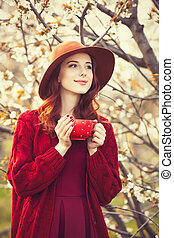 women in red sweater and hat with cup - Portrait of a ...