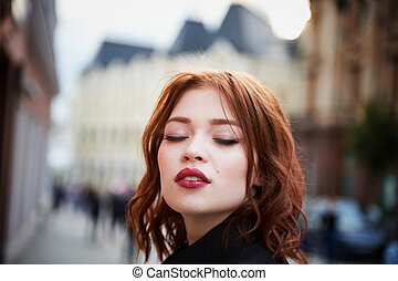 Portrait of a beautiful redhead.Fiery hair and full lips. Walking around the city