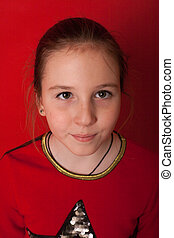 portrait of a beautiful schoolgirl girl on a red background