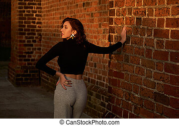 Portrait of a beautiful sensual redhead girl posing in sunset sunlight wearing light grey wide leg high waist jersey trousers and black long sleeve t-shirt casting a shadow on red brick wall background
