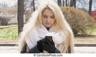 Portrait of a beautiful sexy girl with blond hair, happy smiling. She uses a mobile phone, dials SMS, communicates in the messenger.