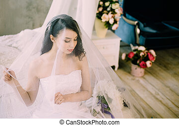 Portrait of a beautiful sexy tender bride with long black or dark hair in the morning at home sitting on bed. Classical fine art wedding. Veil is thrown over her face.