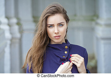 Portrait of a beautiful sexy young woman in dark blue coat