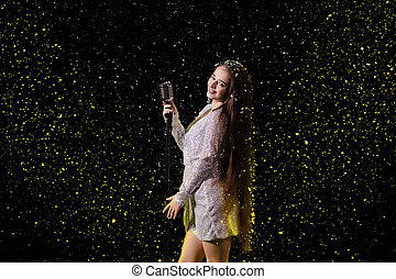 Portrait of a beautiful singer with a vintage microphone against the background of falling snow. Young woman on an empty stage in the rays of yellow studio light close up.