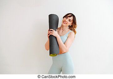 Portrait of a beautiful skinny girl in a sweatsuit holding a rolled-up mat