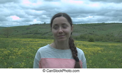 Portrait of a beautiful smiling girl in a field and dense clouds. Happy young woman in a field with yellow flowers and green grass.