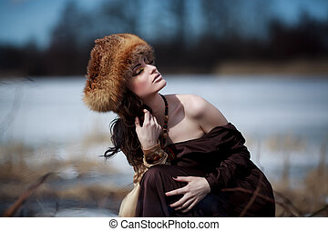 portrait of a beautiful smiling girl in a fur hat
