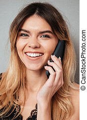 Portrait of a beautiful smiling girl talking on mobile phone