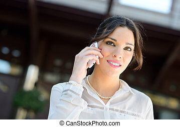 Portrait of a beautiful smiling businesswoman on the phone in a office building