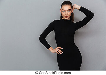 Portrait of a beautiful smiling woman in black dress posing