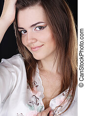 Portrait of a beautiful smiling young girl on black background, tender make up