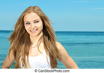 Portrait of a beautiful smiling young lady on the beach...