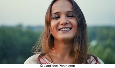 Portrait of a beautiful smiling young woman outdoors. Slow motion