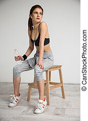 Portrait of a beautiful sports woman resting on the chair