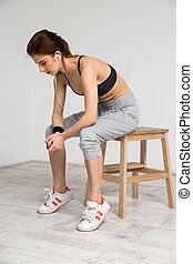 Portrait of a beautiful sports woman sitting on the wooden...