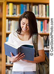 Portrait of a beautiful student reading a book