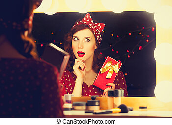 woman with present box near a mirror.