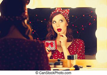 woman with present box near a mirror.