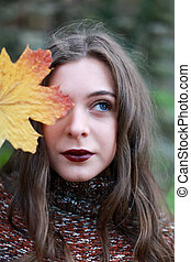 Portrait of a beautiful teenage girl holding a leaf to her face