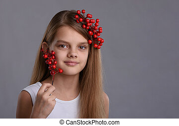 Portrait of a beautiful ten year old girl with a bunch of berries in her hand and hair
